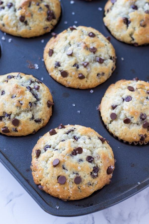 A pan of big, bakery chocolate chip muffins fresh out of the oven.