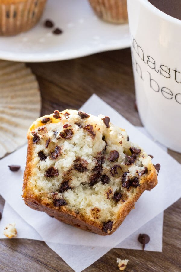 A bakery-style chocolate chip muffin made with sour cream and buttermilk broken in half to show the soft, fluffy muffin texture.