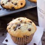 One big, fluffy bakery-style chocolate chip muffin with a cup of coffee and pan full of muffins in the background.