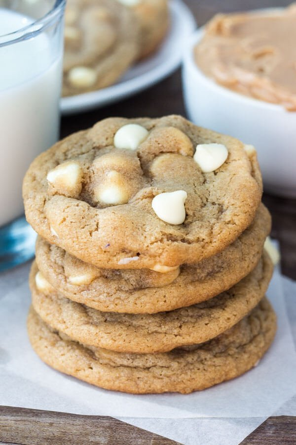 Stack of peanut butter white chocolate chip cookies. Glass of milk and second plate of cookies in the background.