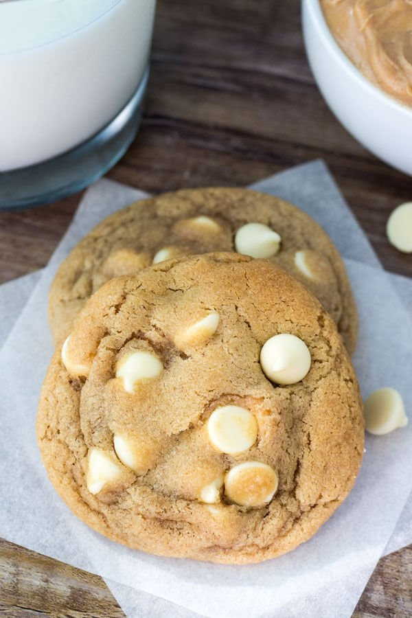 Two peanut butter white chocolate chip cookies on white napkin with white chocolate chips scattered around.
