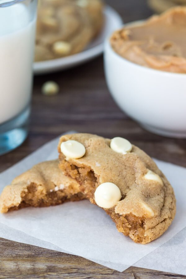 Peanut butter white chocolate chip cookie broken in half. Glass of milk and bowl of peanut butter in the background.