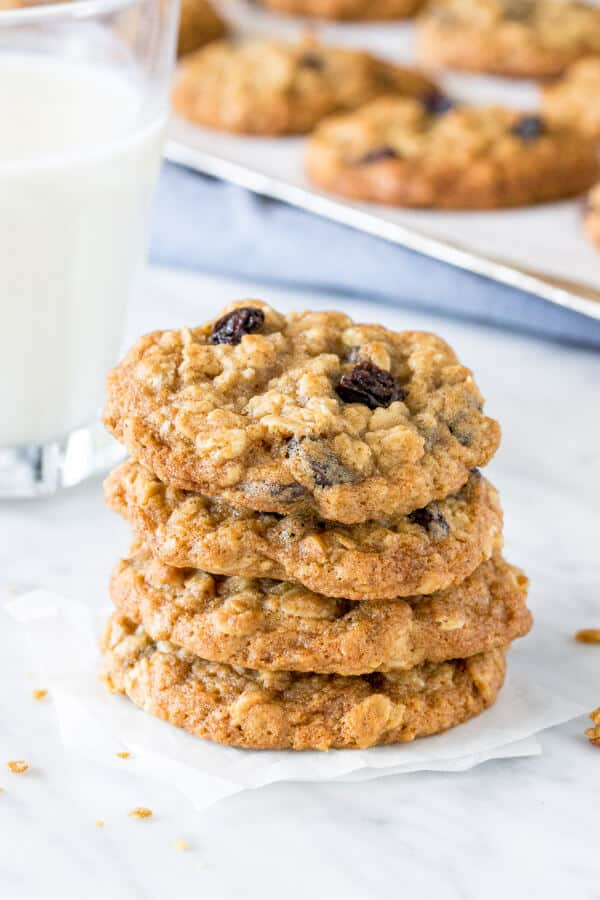 A stack of oatmeal raisin cookies with a glass of milk