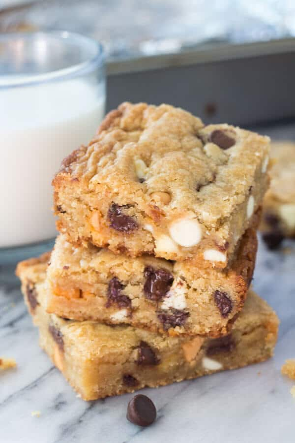 Side shot of 3 stacked triple chip cookie bars with a glass of milk and the cookie bar pan in the background.