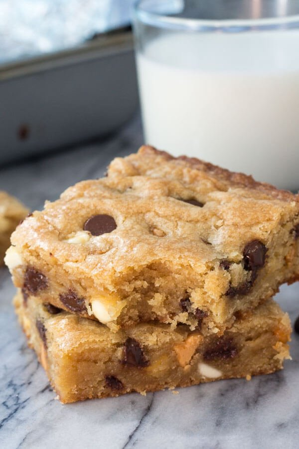 Stack of 2 triple chip cookie bars with a bite taken out of the bar on top. A glass of milk and the pan in the background.
