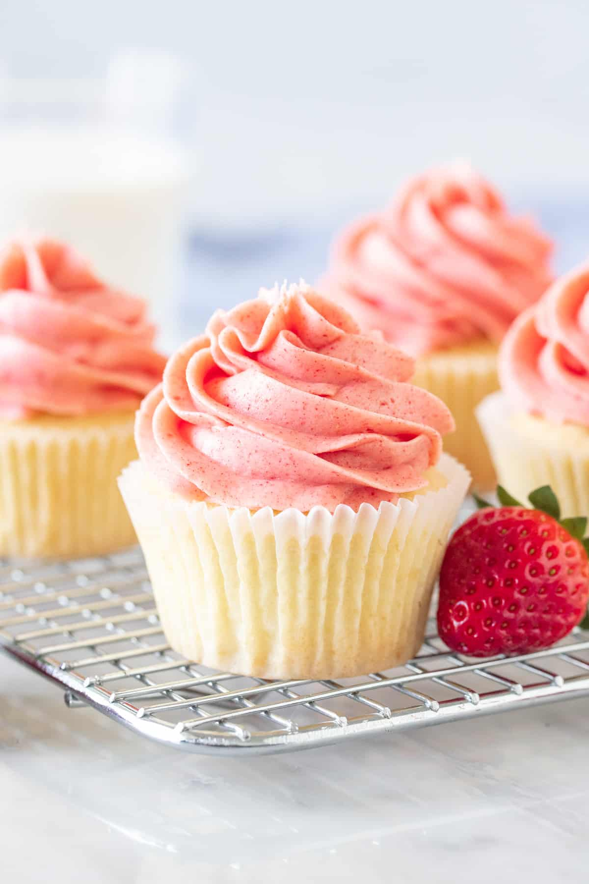 Vanilla cupcakes with strawberry frosting on a wire rack