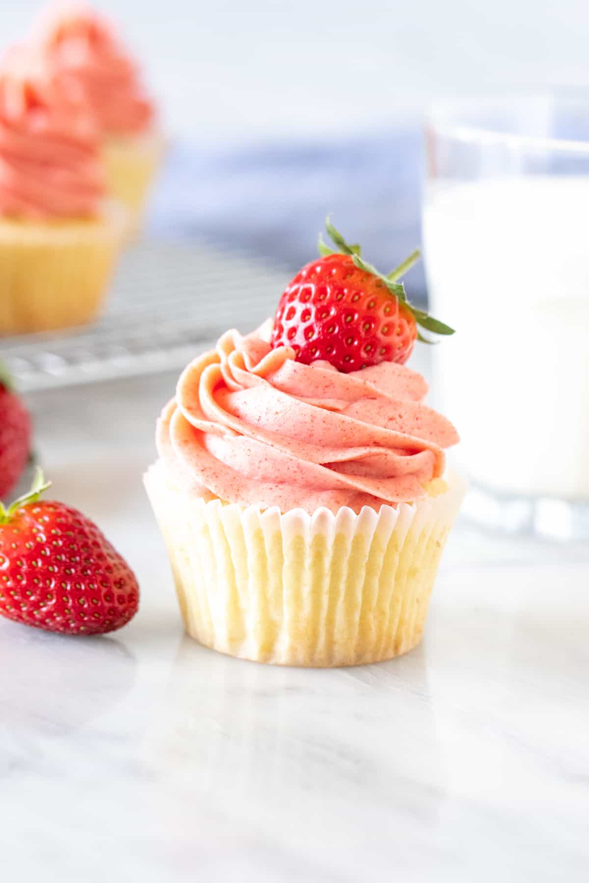 Vanilla cupcake with strawberry frosting and a glass of milk