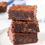 A stack of 3 triple chocolate brownies from the side.