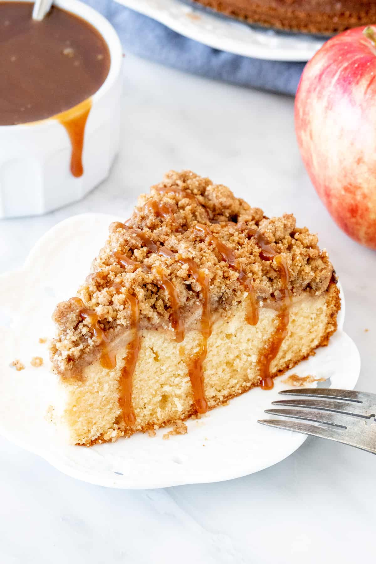 Slice of apple coffee cake with a drizzle of caramel sauce.