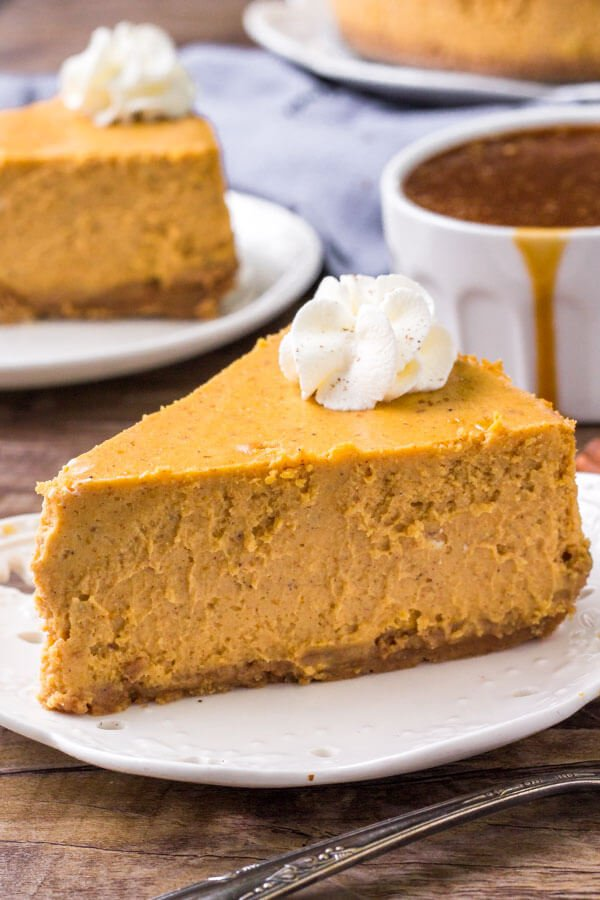 A slice of pumpkin cheesecake topped with whipped cream.