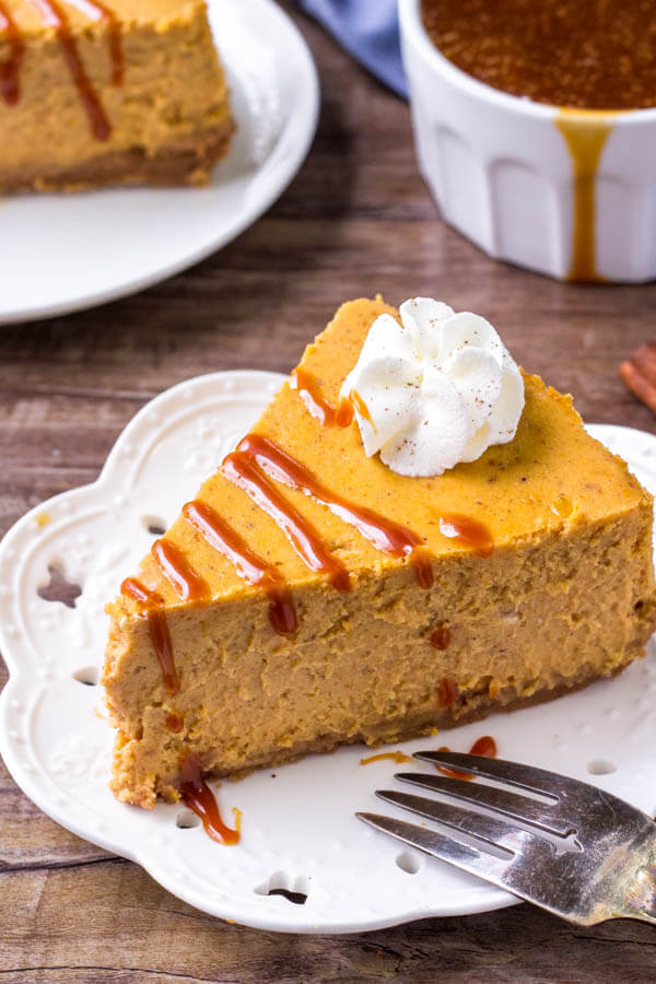 Pumpkin Cheesecake with graham cracker crust and a drizzle of salted caramel sauce. Smooth, creamy & filled with pumpkin spice.