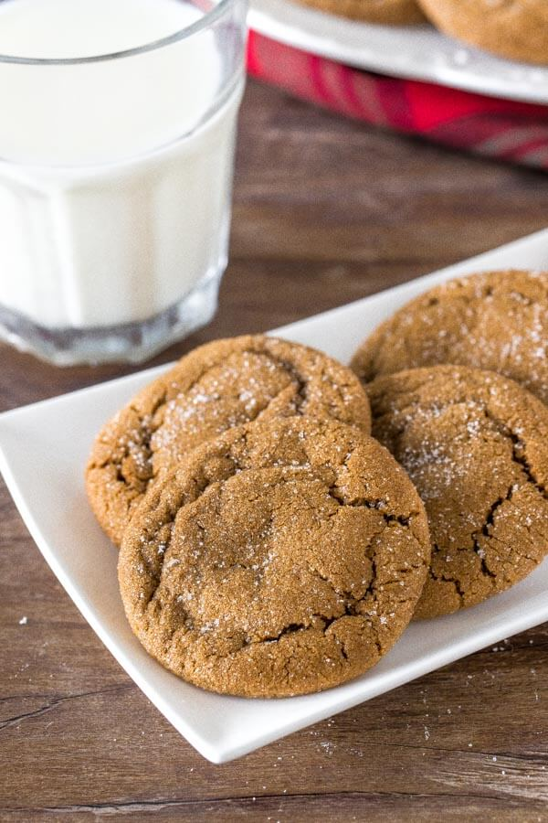 A plate of soft, chewy ginger molasses cookies rolled in sugar with a glass of milk