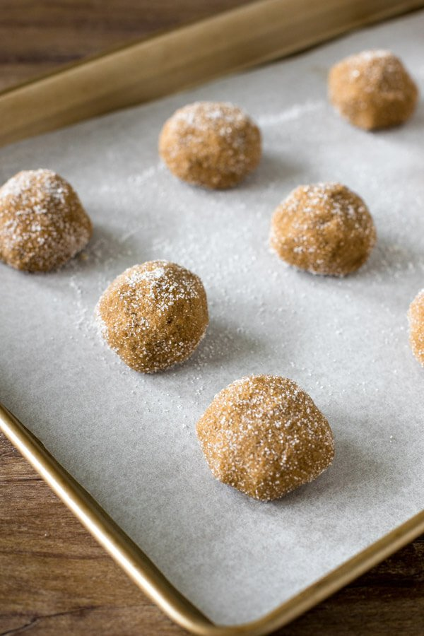 A cookie tray of ginger molasses cookie dough balls rolled in sugar
