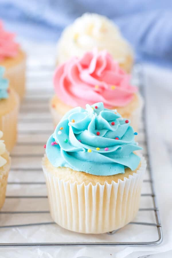 Vanilla cupcakes with colored frosting on a cooling rack.