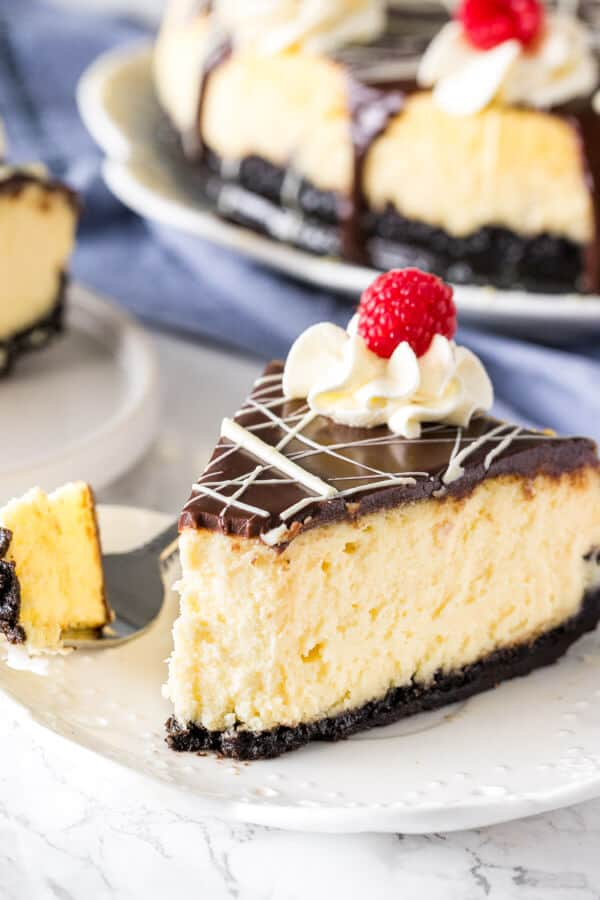 A slice of white chocolate cheesecake with a bite taken out to show the smooth, creamy texture.