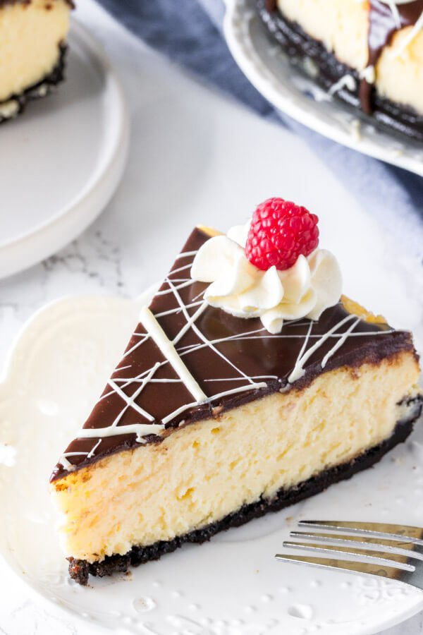 A slice of creamy white chocolate cheesecake with chocolate ganache and a drizzle of white chocolate on top.