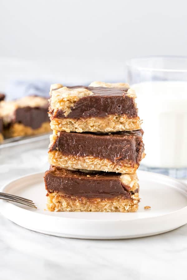 Stack of 3 oatmeal fudge bars on a plate with a glass of milk.