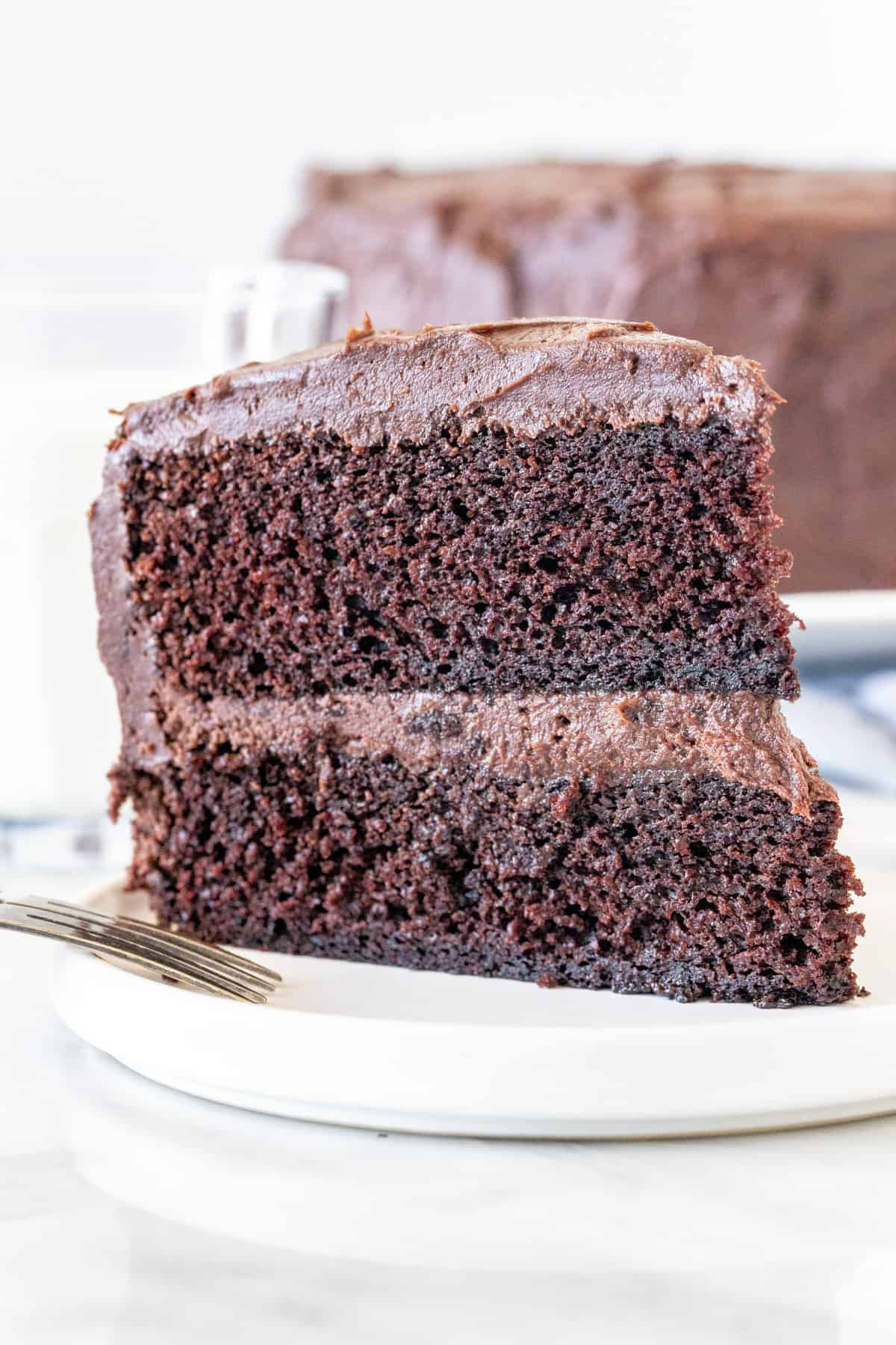 Slice of chocolate cake with chocolate frosting.
