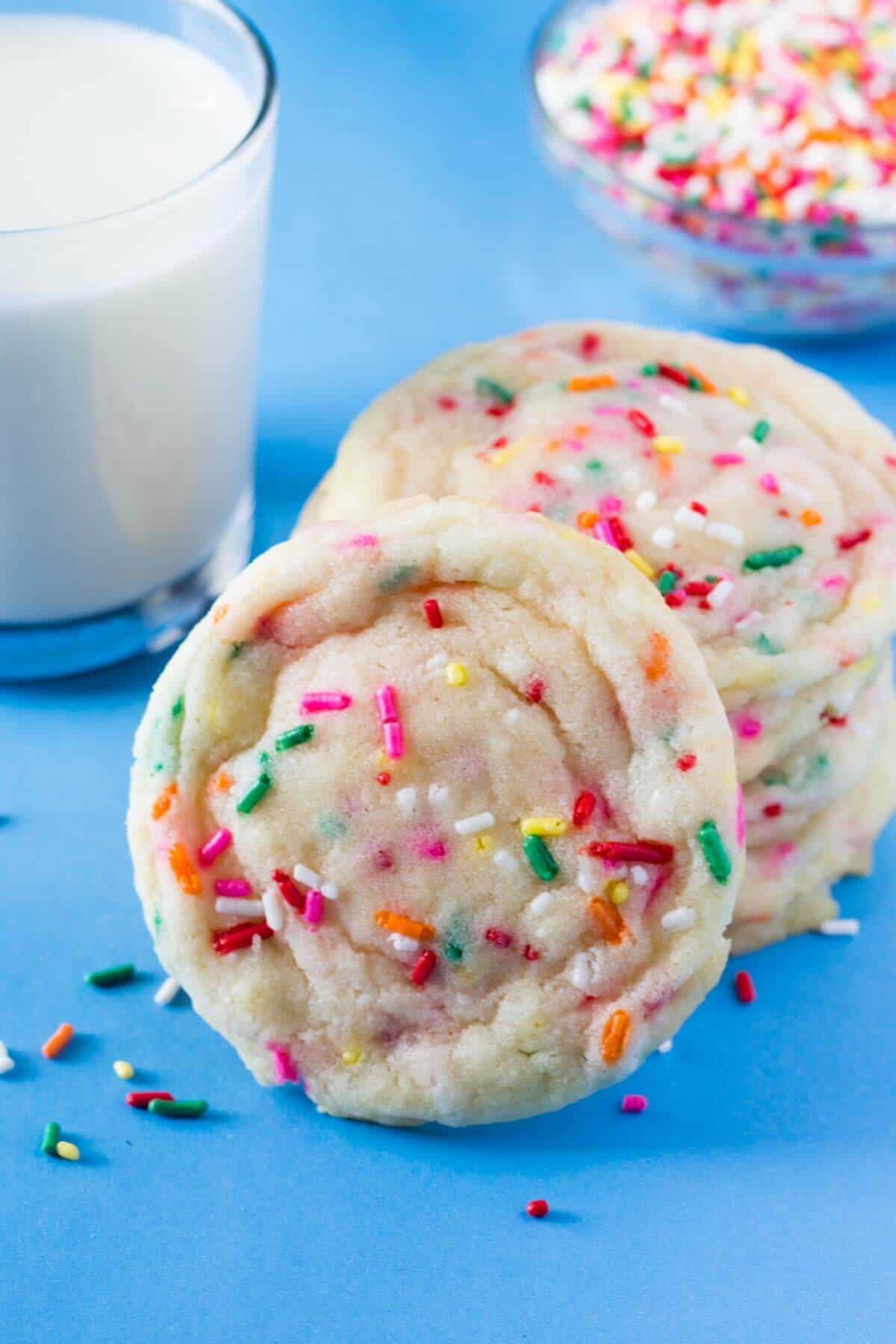 A stack of funfetti cookies with a glass of milk and a bowl of sprinkles.