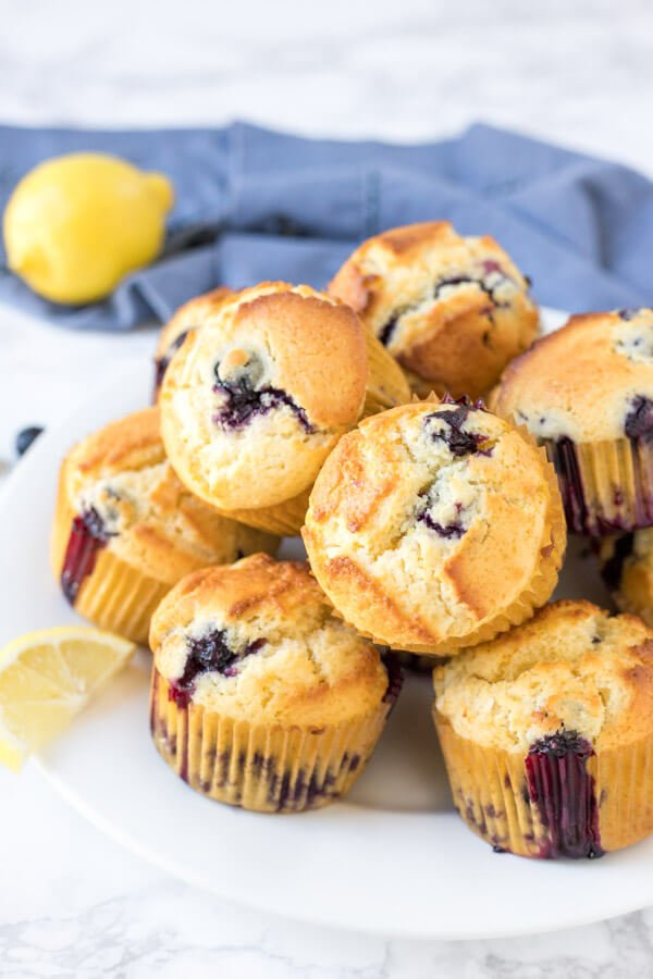 A plate of lemon blueberry muffins with golden tops and tons of blueberries.