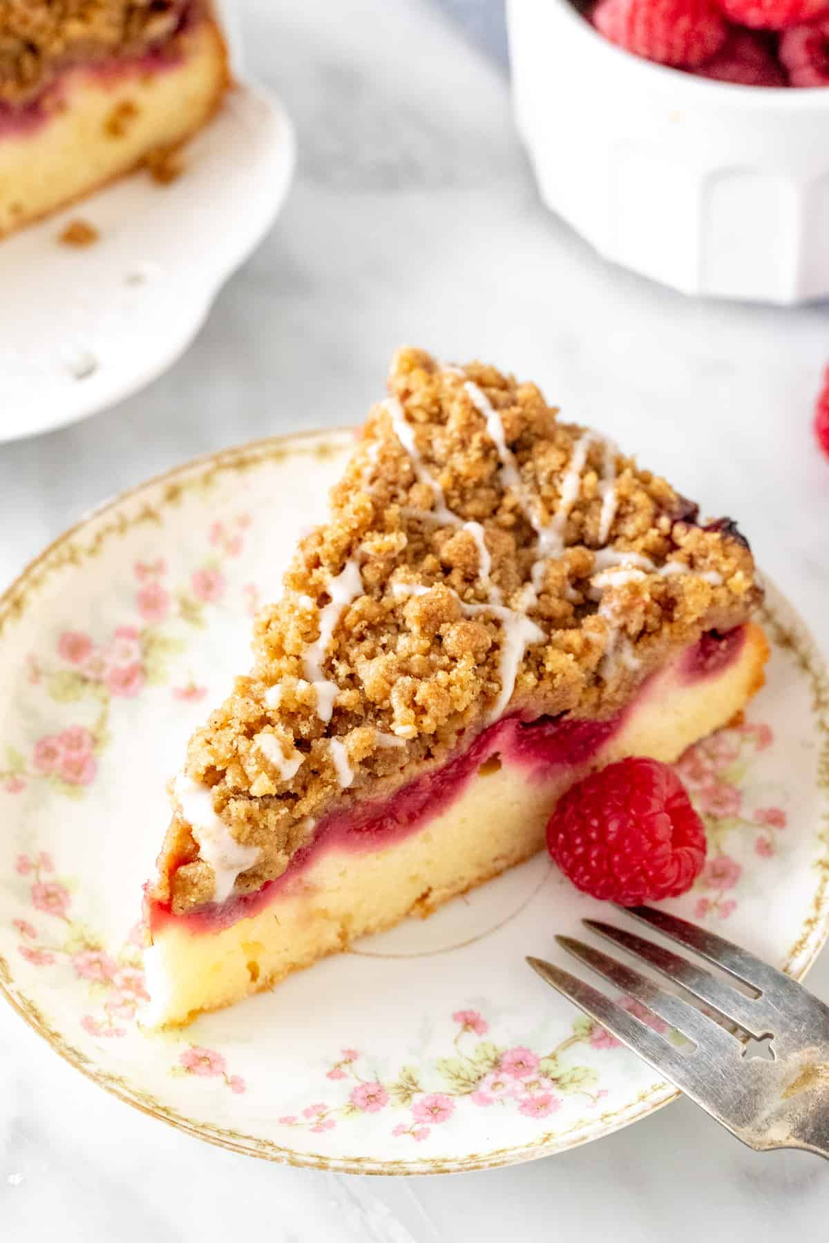 Slice of streusel topped cake with a layer of raspberries.