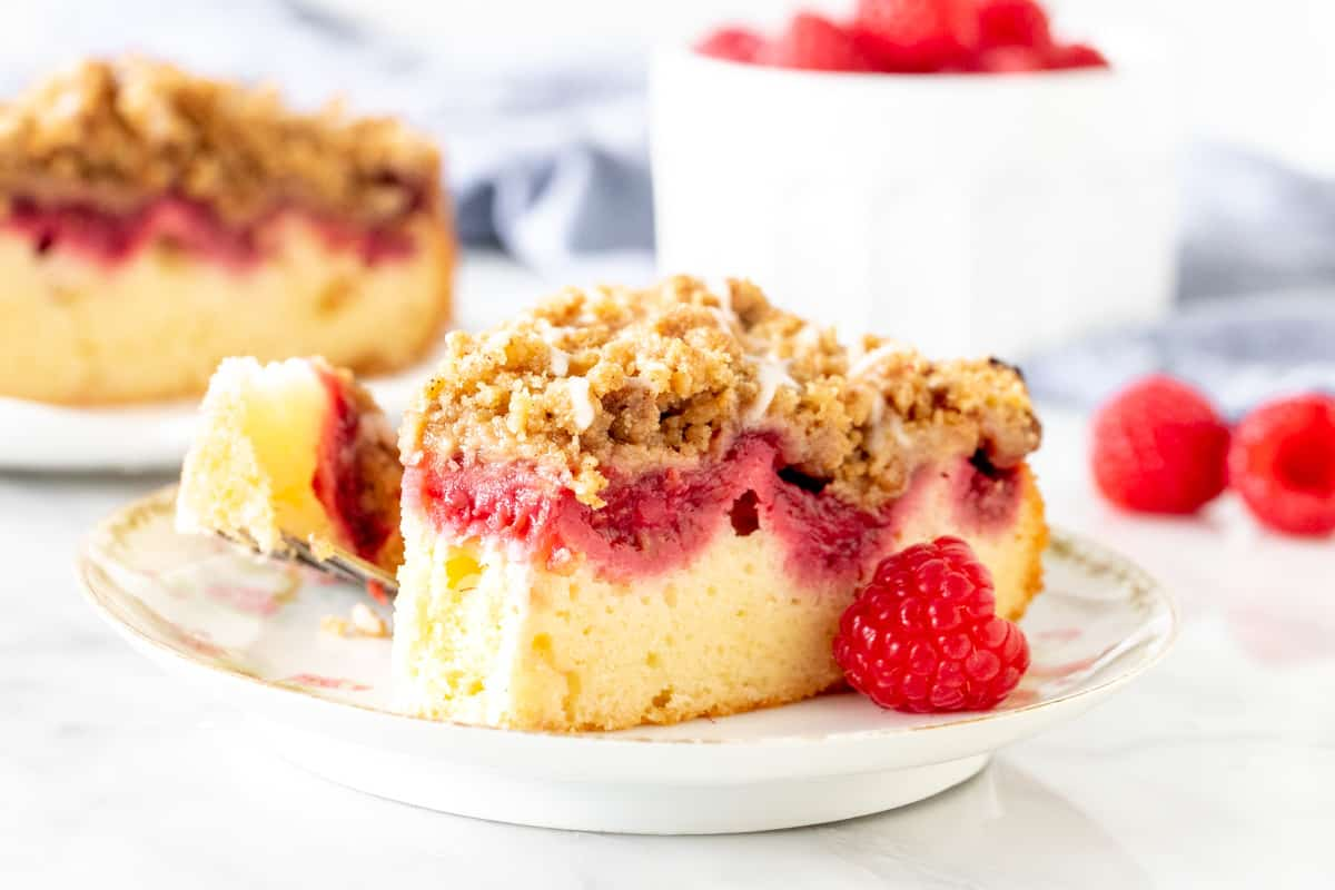 Slice of raspberry crumb cake with a bite taken out of it.