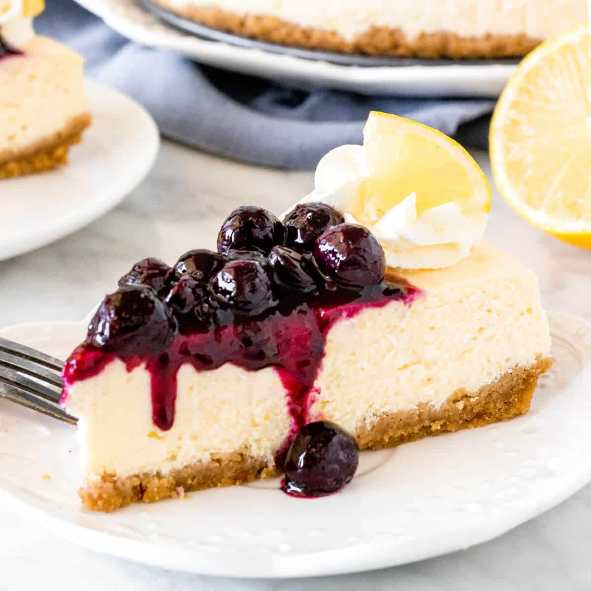 Slice of lemon cheesecake with blueberry sauce