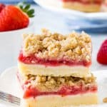 Stack of 2 strawberry crumb bars on white plate with bowl of strawberries.