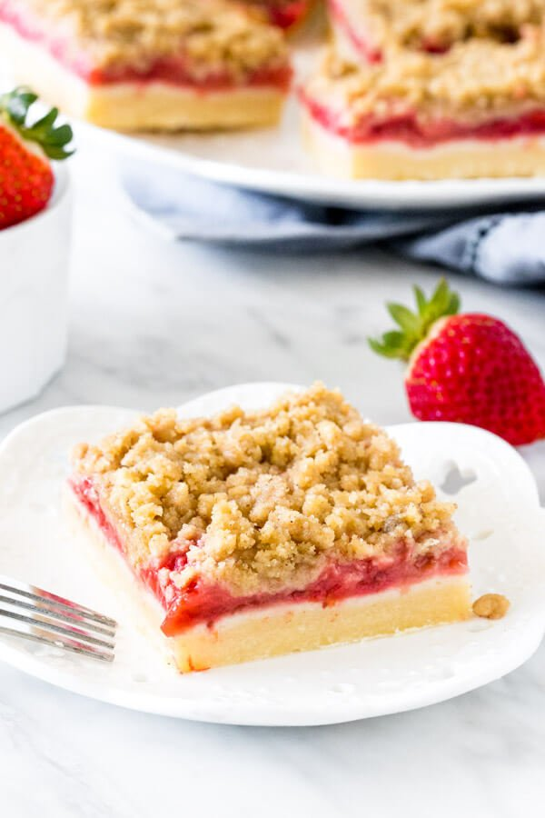 Strawberry bar with crumb topping on a white plate with a fork.