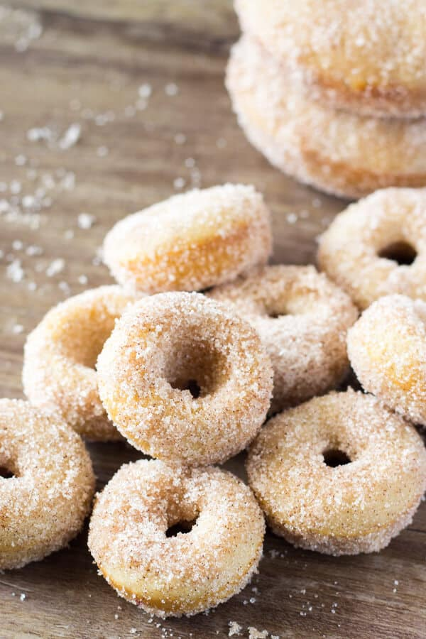 Mini Cinnamon Sugar Doughnuts just like the fair! With golden edges, a delicious coating of cinnamon sugar, and baked instead of fried - these are the PERFECT copycat recipe! www.justsotasty.com