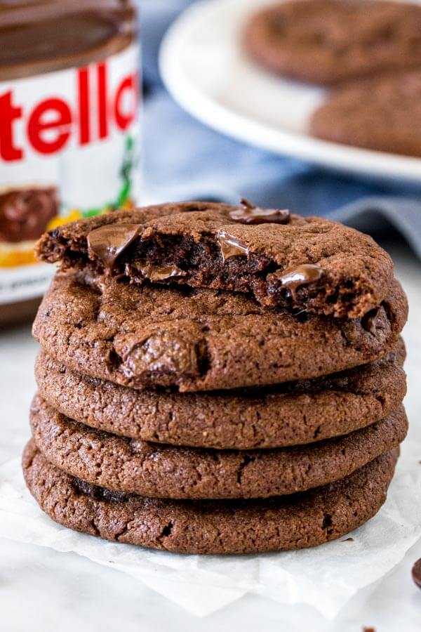 Stack of chocolate Nutella cookies with the top cookie broken in half.