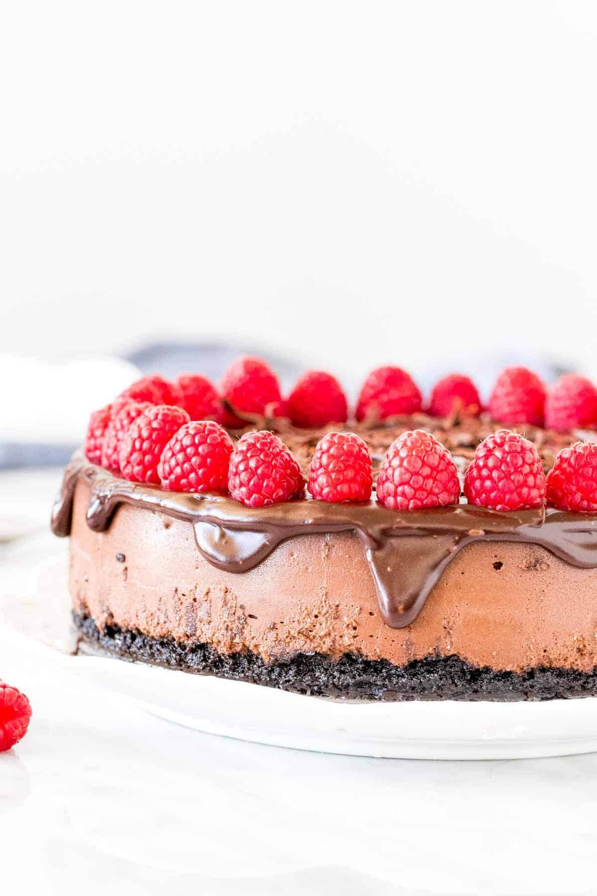 Chocolate cheesecake with chocolate ganache and raspberries on top.