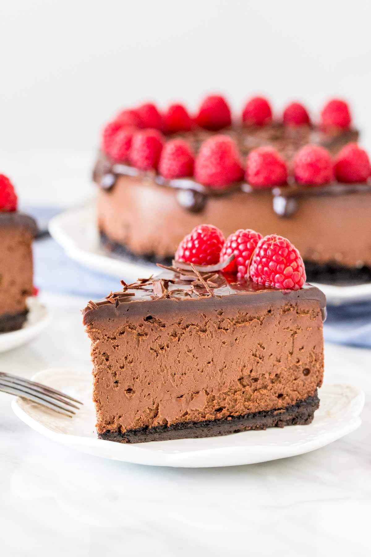Slice on chocolate cheesecake on a plate with plate of cheesecake in background.