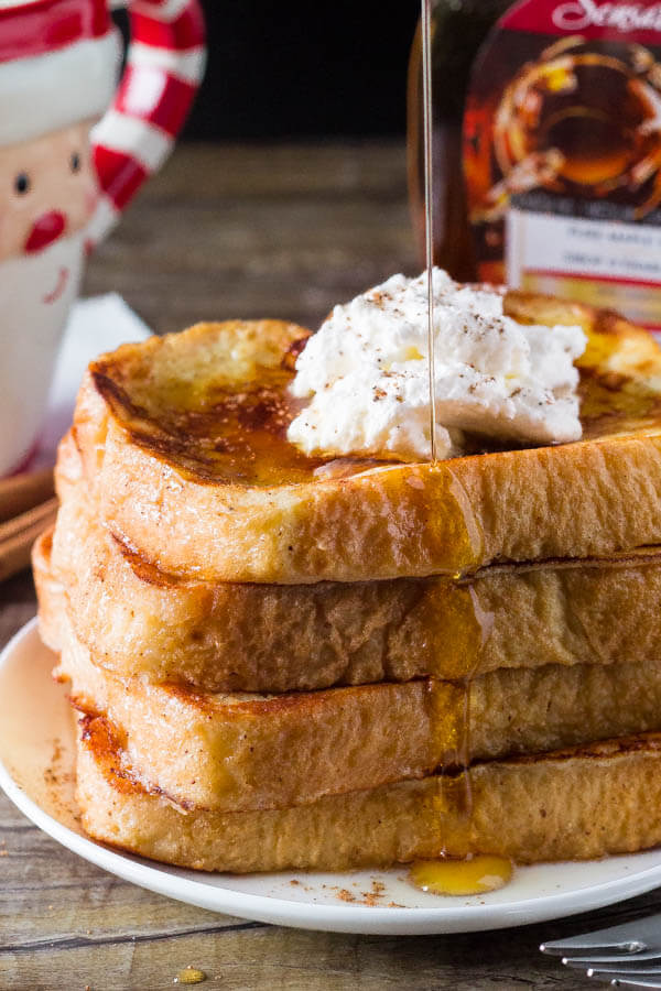 Pouring maple syrup on a stack of eggnog french toast.
