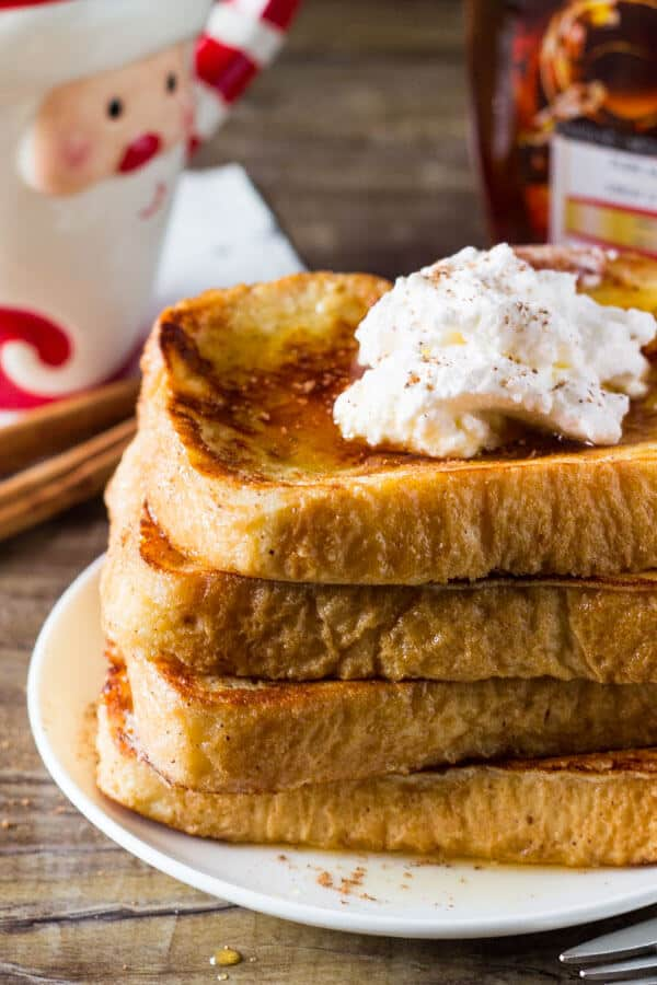 A plate of 4 pieces of eggnog French toast stacked on a white plate and topped with whipped cream and maple syrup.