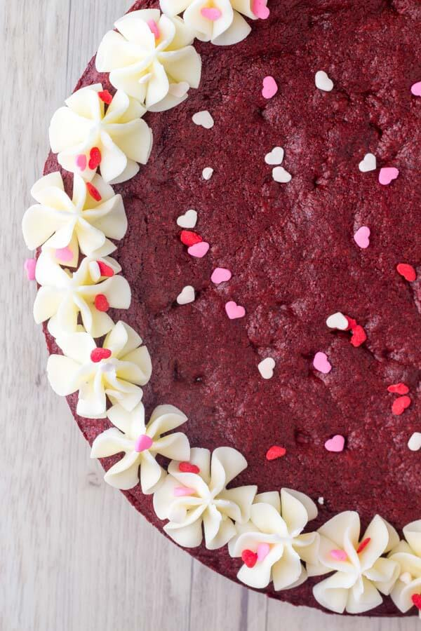 Red Velvet Cookie Cake. A giant red velvet chocolate chip cookie made into a cake and frosted with cream cheese frosting. Made from scratch & perfect for Valentine's or Christmas. www.justsotasty.com