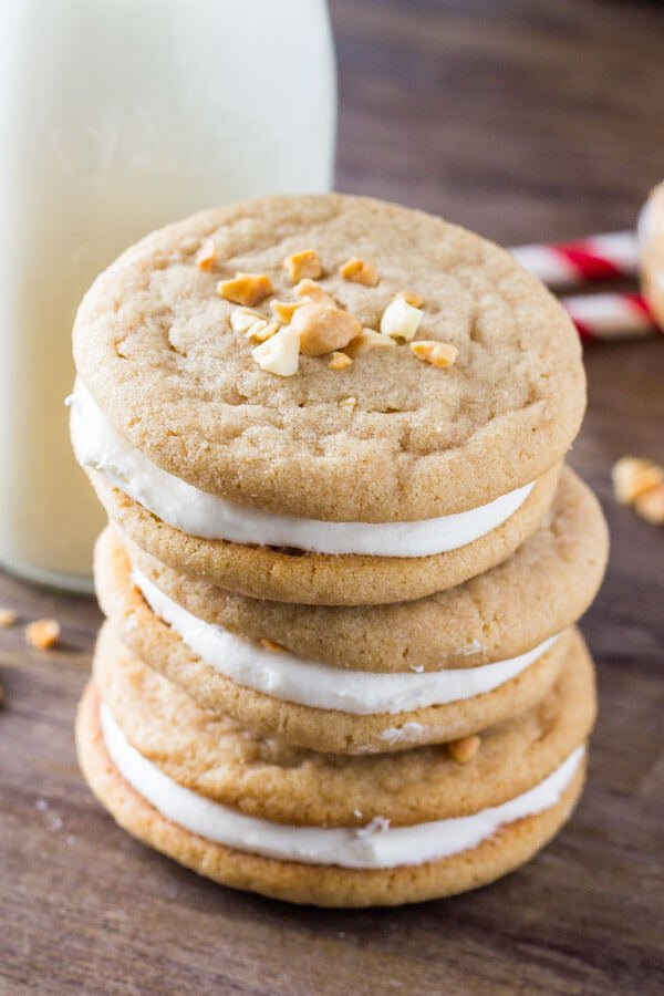 Stack of 3 fluffernutter cookies with a glass of milk and 2 straws in the background.