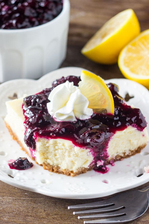 Lemon Blueberry Cheesecake Squares. Smooth & creamy lemon cheesecake with a graham cracker crust and blueberry sauce. Perfect for spring! www.justsotasty.com