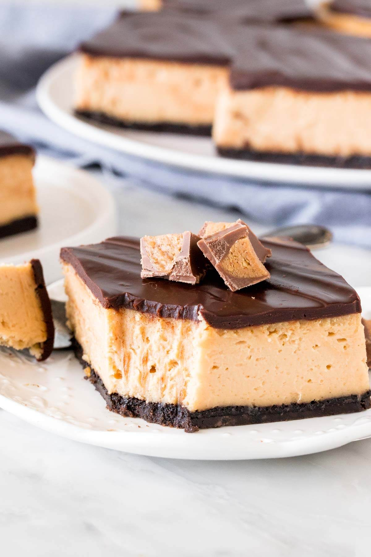 Slice of peanut butter cheesecake bars topped with chocolate and peanut butter cups.