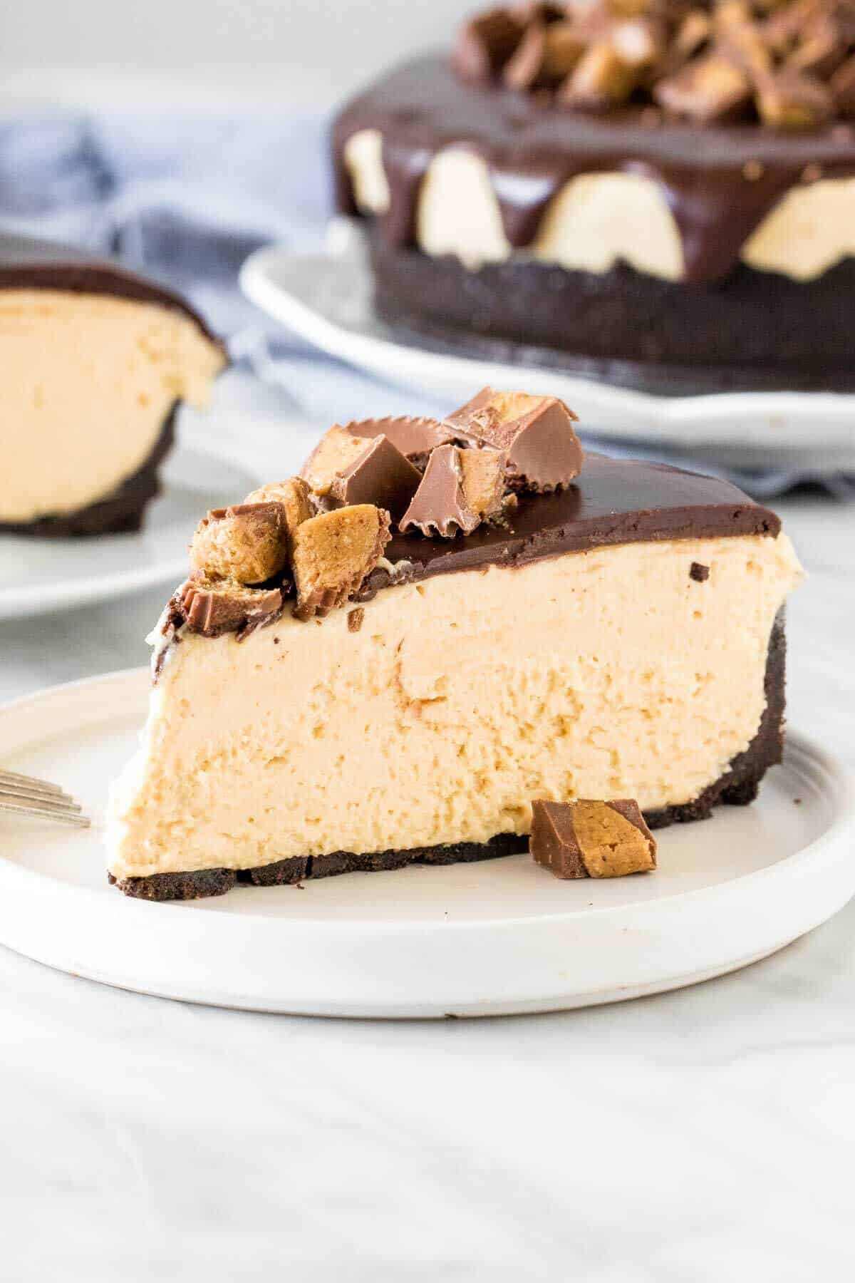 Slice of no-bake peanut butter cheesecake with peanut butter cups on top.