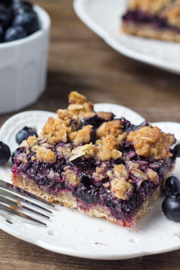 These blueberry oatmeal crumble bars are bursting with juicy blueberries, and filled with crunchy oatmeal crumble. Delicious for breakfast or dessert - you'll love this easy recipe!