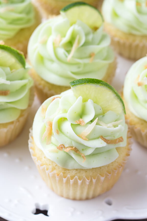 Overhead view of a plate of coconut cupcakes with lime buttercream frosting.
