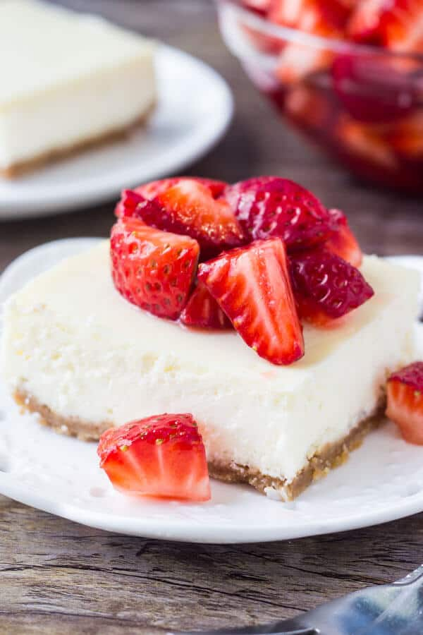 Slice of fresh strawberry cheesecake bar with a slice of plain cheesecake and a bowl of chopped strawberries in the background.