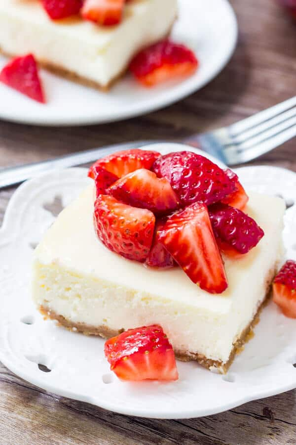 Cheesecake bar topped with chopped strawberries on a white plate. Fork and second cheesecake bar in the background.