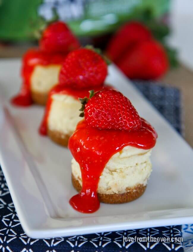 Three Miniature Strawberry Cheesecakes on a white rectangular plate