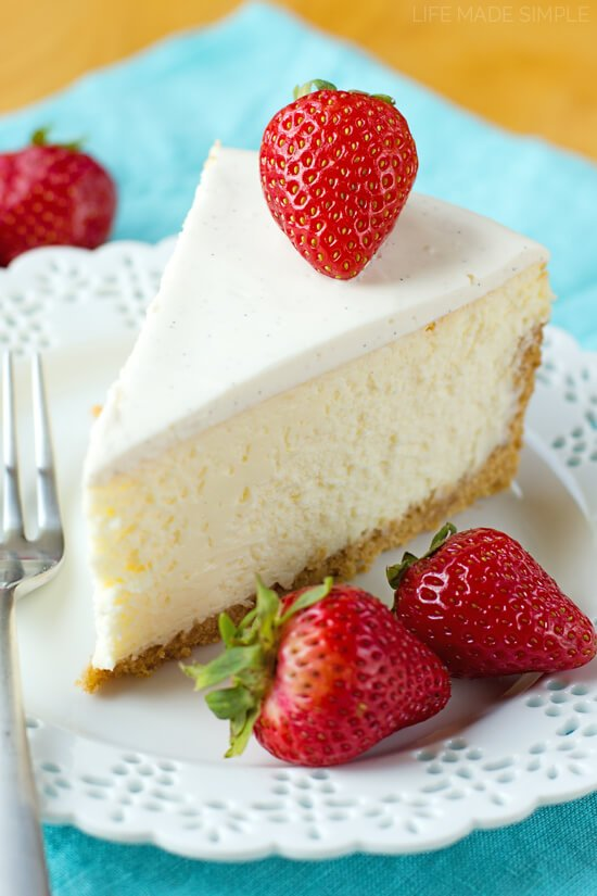 Slice of New York Cheesecake on white plate with blue napkin. Topped with a strawberry.
