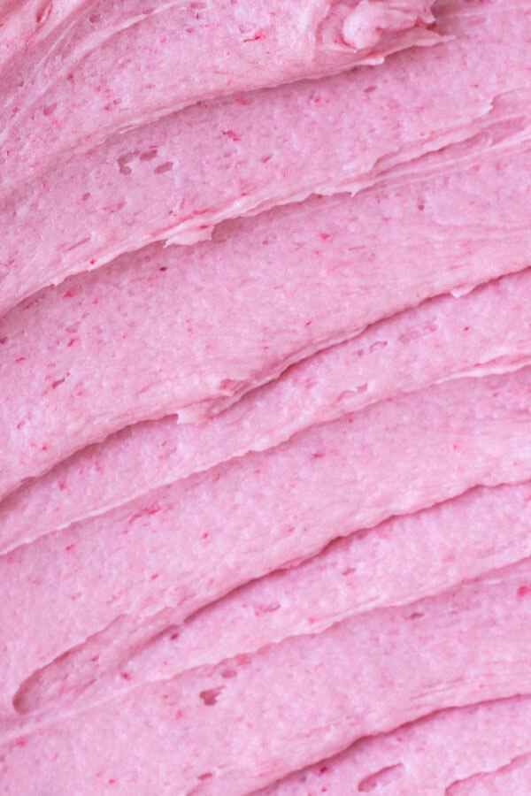 Overhead closeup shot of raspberry buttercream frosting slatherd on a sheet cake