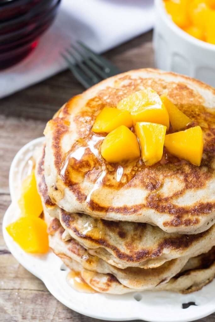 Overhead view of a stack of brown sugar peach pancakes on a white plate & drizzled with syrup and chopped peaches.