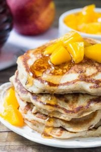 Stack of brown sugar peach pancakes drizzled with syrup and topped with chopped peaches. Jar of syrup of bowl of chopped peaches in the background.