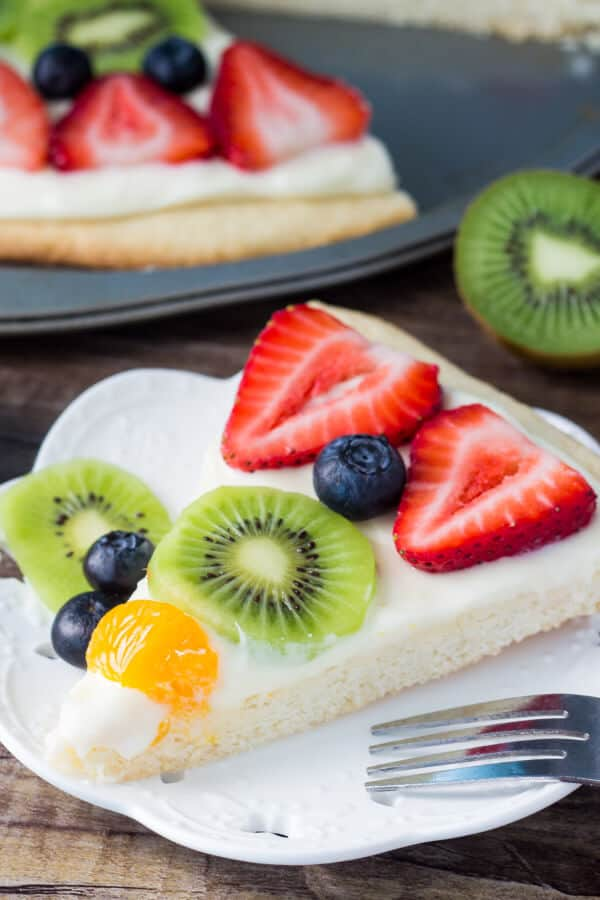 Slice of sugar cookie pizza on a white plate. Full pizza and kiwi in the background.